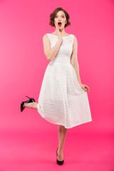 Full length portrait of a shocked girl dressed in dress