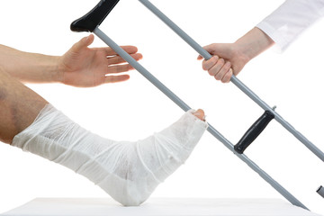 doctor gives a crutch to a man with a broken leg