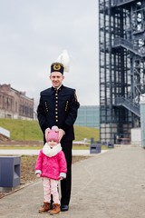 Black coal miner in gala uniform with his child