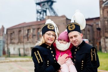 Polish black coal miners family in gala uniforms with child.