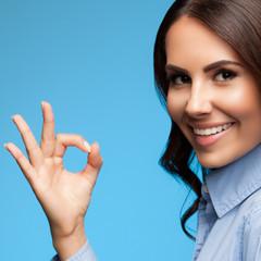 Showing okay gesture businesswoman, on blue