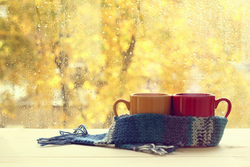 warming autumn atmosphere/ two cups in  blue scarf on table in the background of  window with drops after rain