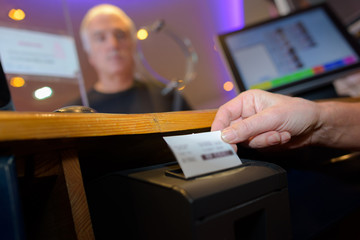 Ticket being printed from machine in booth