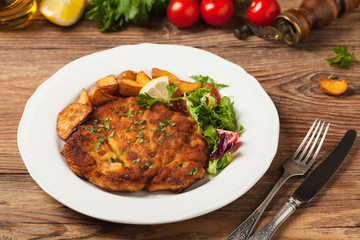 Chicken schnitzel, served with roasted potatoes and salad.
