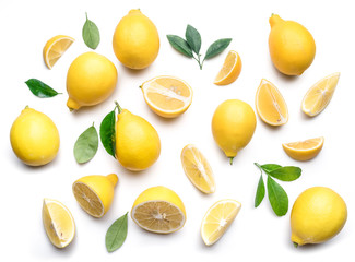 Ripe lemons and lemon leaves on white background. Top view.