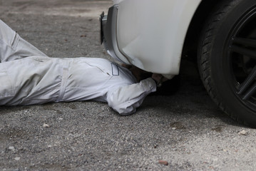 Professional mechanic man in white uniform lying down and repairing under car. Car maintenance concept.