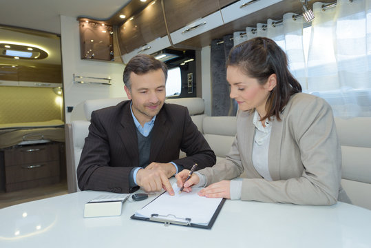 Lady signing contract inside camper van