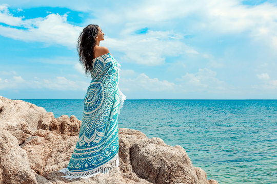 beautiful young woman covered with blanket with on the beach