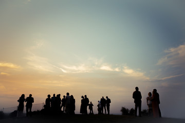Silhouettes of people gathered at an event with magnificent sky's shades in the background.