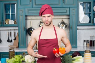 Macho in chef hat, apron point hand at pepper