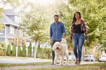 Couple Walking Dog Along Suburban Street