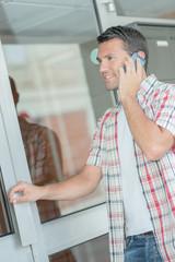 Man on telephone, holding door handle