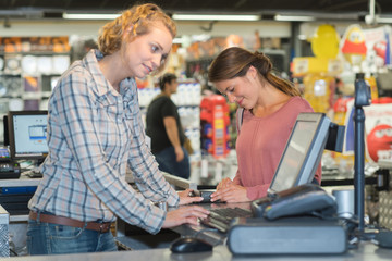 female customer paying at cash desk with terminal in supermarket