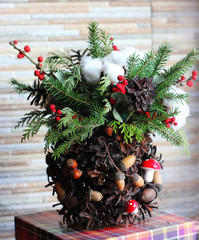 New year composition of fir branches, cones, Christmas balls, dried oranges and cinnamon in a brown wooden pot