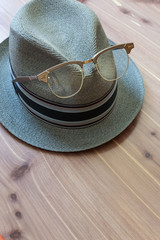 Vintage hipster concept with retro fedora hat, metal horn rimmed glasses perched on the front, neutral wood background, copy space, vertical aspect