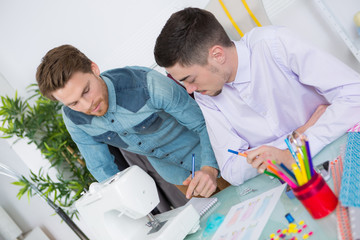 two fashion designers using sewing machine in a studio