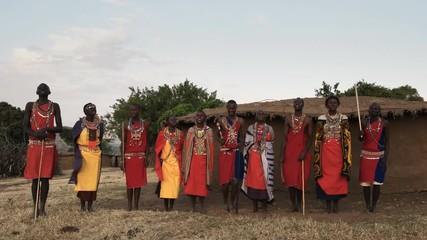 Wall Mural - maasai women and men sing then dance together in pairs at a village near masai mara in kenya