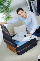 man putting shirt into a suitcase