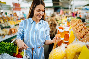 Portrait of beautiful woman holding shopping basket at marketplace