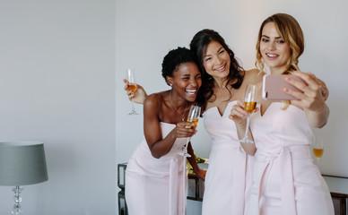 Beautiful bridesmaids taking selfie