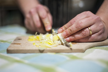 woman's hands cut vegetables on chopping board