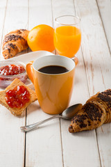 croissant  mug of coffee orange juice and toast with jam