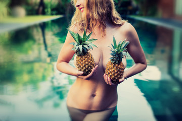 Woman holding pineapples in front of her breasts