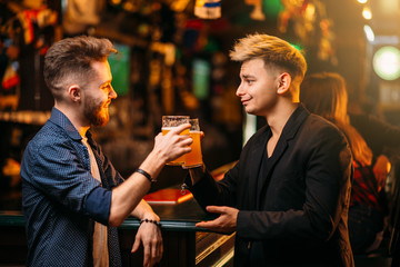 Men raised their glasses with beer in a sport pub