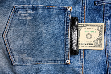 Black leather wallet with money in back blue jeans pocket denim background texture.