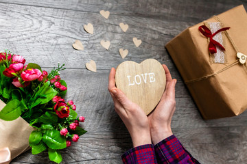 Female hand holding a wooden heart, Valentine's Day, romantic photos . with a gift and a bouquet of flowers, with hearts and gifts, suitable for advertising