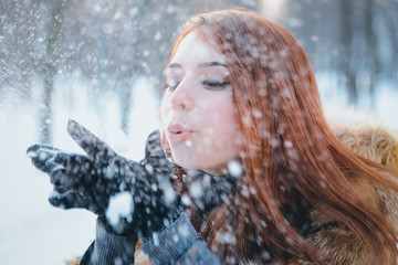 Fashionable beautiful, smile red-haired girl in a snowy forest in a fur coat with fur. Portrait of a brown-haired girl. Winter, snow Women's fashion portrait.