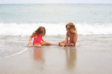 Two little girl sitting on the beach.