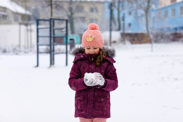 Adorable little kid girl in colorful clothes playing outdoors during snowfall