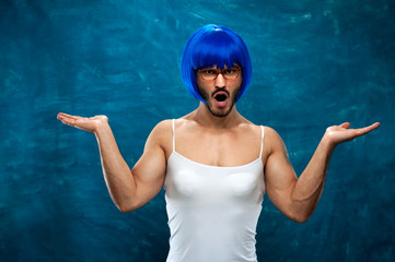 Positive young male cross dressing person wearing blue wig and female cloth posing on blue background.