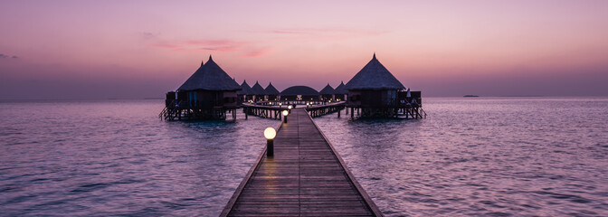 A great vacation on a tropical island. Resort on the tropical islands. Maldives. Bungalows over the water at sunset.