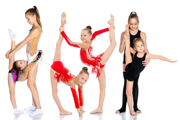 A group of girls gymnasts perform exercises.