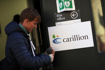 A worker pretends to unscrew a sign at a Carillion construction site in central London