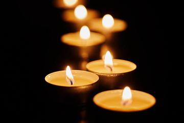 Burning votive candles on dark background