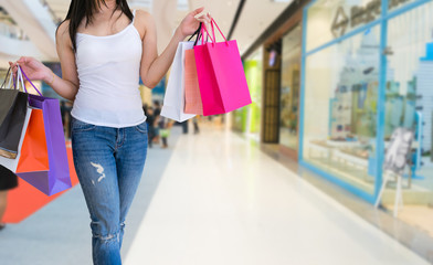 Female walks hands holding shopping bags in the mall