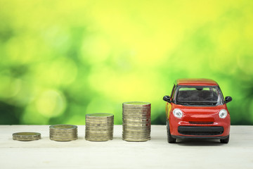 Car loan concept, stack of money and car toy on old wood table, investment and business concept