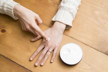 ハンドクリームを使う女性の手