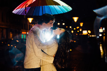 young couple under an umbrella kisses at night on a city street.