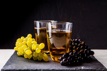 Picture of glasses with juice and bunches of grapes on stone board