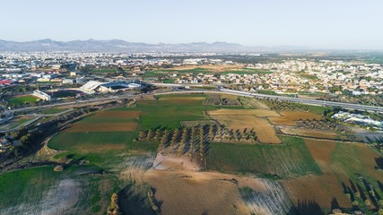 Aerial bird's eye view of GSP football stadium, highway A1 at Latsia, Nicosia, Cyprus. The soccer field, athlete track, seats and auxiliary pitch of Pancyprian Gymnastic Association Stadium from above