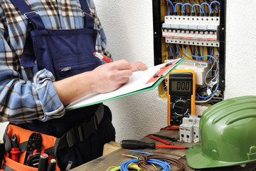 Young electrician technician at work on a electrical panel