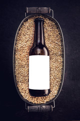 Blank label on the beer bottle in basket full of wheat