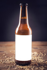 Blank label on the beer bottle with wheat on dark background