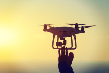 silhouette of hands reaching a flying drone which taking photo over sunrise sea