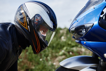 Close up sideways view of blue motorcycle and self determined young male rider wearing black...