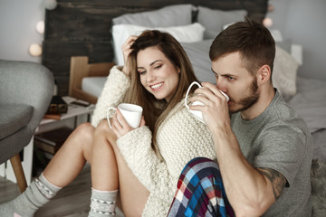 Affectionate couple drinking morning coffee at bedroom